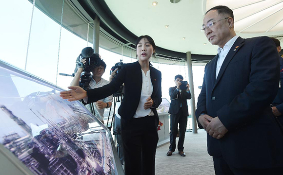 Hong Nam-ki (right), the minister of economy and finance, receives a briefing from an official at a SK Innovation plant in Ulsan on June 13, 2019. [Photo provided by the Ministry of Economy and Finance]