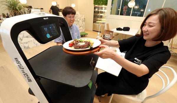 A self-navigating robot delivers food to customers at Merry-Go Kitchen in Seoul, a robot-serving restaurant run by Woowa Brothers. [photo by Kim Ho-young]