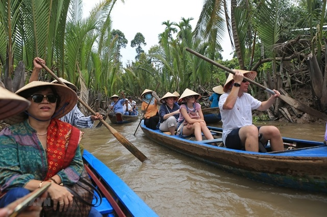 Tourists take boat trips in the southern province of Tien Giang. - VNA/VNS Photo