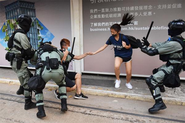 5일(현지시간) 홍콩 경찰이 마스크를 쓴 커플 시위대를 진압하고 있다. 전날 캐리 람 홍콩 행정장관은 사실상 계엄령에 해당하는 `긴급정황규례조례(긴급법)`를 선포하고 5일 0시를 기해 복면금지법을 시행했다. [AFP = 연합뉴스]