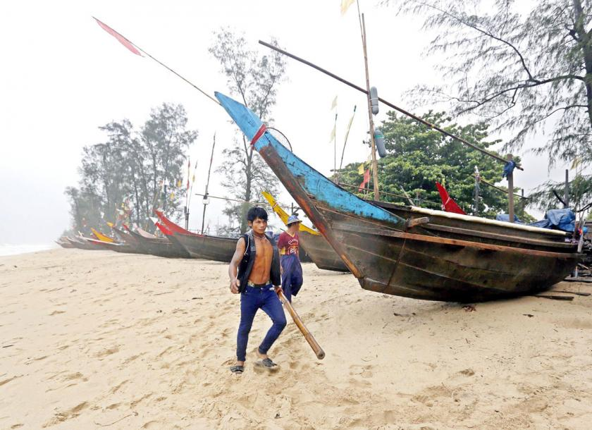 A man holds a bamboo as he walks pass near the fishing boats at the MaungMaKan village in Dawei city. Photo - EPA