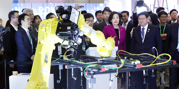 South Korean SMEs and Startups Minister Park Young-sun (second from right) and Thai Higher Education, Science, Research and Innovation Minister Suvit Maesincee (first from right) look at a co-op robot during a startup expo named ComeUp held on the sidelines of the Korea-Association of Southeast Asian Nations (ASEAN) special summit at the BEXCO exhibition hall in Busan on Monday. (Courtesy of Yonhap News)