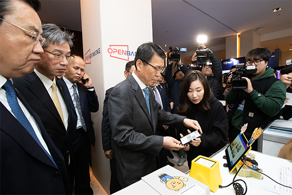 Financial Services Commission Chairman Eun Sung-soo (fourth from left) tries out the open banking service at an experience booth in Seoul, on Dec.18, 2019. [Photo provided by FSC]