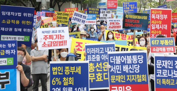 Citizens hold signs condemning the gov't property policies in Seoul on July 18, 2020. [Photo by Yonhap]