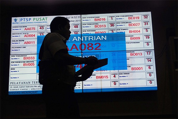 A man walks past an electronic information board at the Investment Coordinating Board