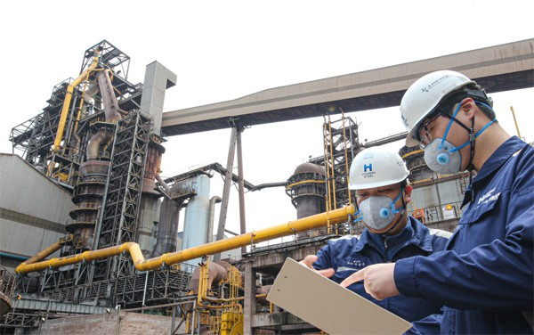 현대제철 직원들이 지난 13일 당진제철소의 고로 주변 시설을 점검하고 있다. 사진 속 노란색 파이프가 고로 오염물질을 줄여주는 `가스 청정 밸브`다. [사진 제공 = 현대제철]