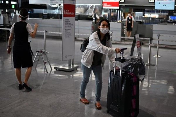 A woman walks with her luggage at the Narita International Airport in Narita, Chiba Prefecture on Aug 19, 2020. (AFP file photo)