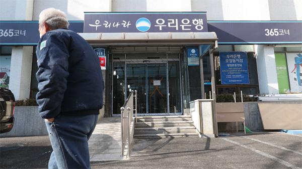 서울 중구에 위치한 우리은행 점포가 폐점한 가운데 한 노인이 영업점 앞을 지나가고 있다. [이승환 기자]