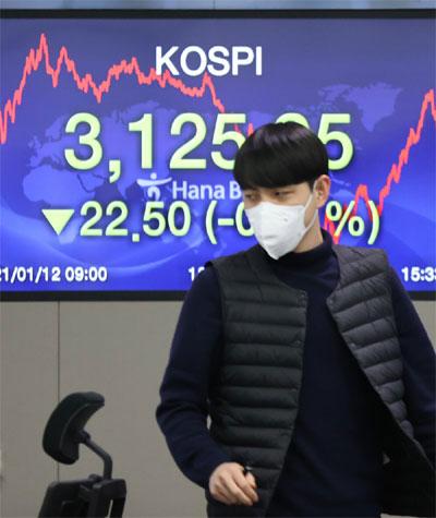 코스피가 3125.95에 거래를 마친 12일 오후 서울 중구 하나은행 딜링룸에서 한 딜러가 자리로 향하고 있다. [사진 = 연합뉴스]