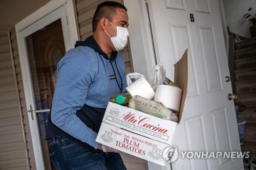 지난 16일(현지시간) 미국 롱아일랜드에서 온두라스 출신의 불법체류자가 기부물품을 집안으로 나르고 있다.