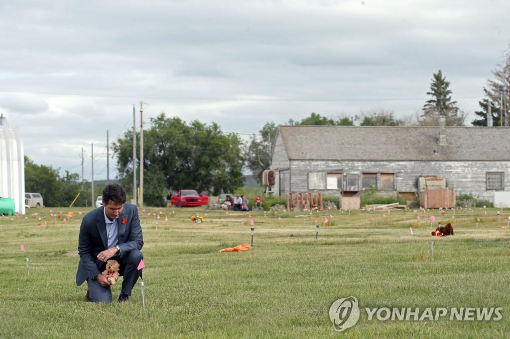 쥐스탱 트뤼도 캐나다 총리가 6일(현지시간) 751기의 무표식 묘지가 발견된 서스캐처원주 원주민학교 터에서 무릎을 꿇고 희생자를 기리고 있다. [로이터=연합뉴스]