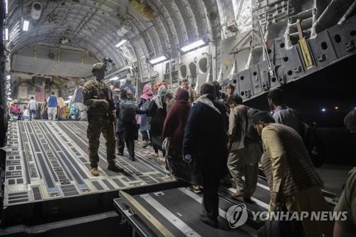 Refugiados afganos toman un avión de transporte bajo seguridad estadounidense